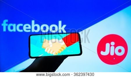Mobile Phone With A Handshake Screen And Facebook And Jio In The Background