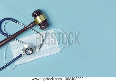 Brown Gavel And A Medical Stethoscope On Blue Background. Symbol Photo For Bungling And Medical Erro