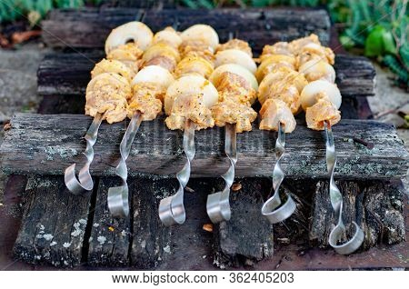 Raw Chicken Meat Barbecue On Defocused Metal Curved Skewers With Rough Rustic Wooden Background. Hom