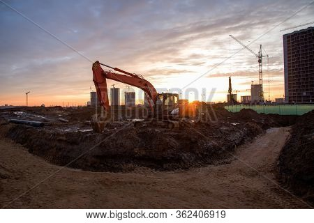Red Excavator At Building Under Construction Against The Background Sunset. Hydraulic Backhoe On Ear