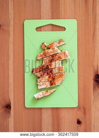 Grilled Turkey Meat Steak Sliced On Cutting Board Over Wooden Tabletop. Perfect Ready-to-eat Turkey