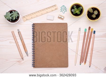 Desk top with eco friendly office supplies such as wooden pen, pencils and brown paper notebook with copy space