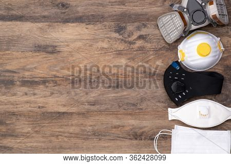 Different protective masks on wooden background, top view with copy space