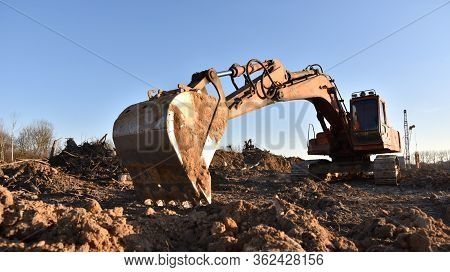 Large Excavator Working At Construction Site. Backhoe During Earthworks On Sand Open-pit. Digging Gr