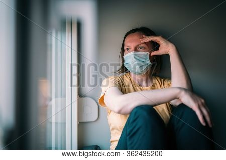 Woman In Self-isolation During Virus Outbreak Looking Through Window. Worried Female Person With Pro