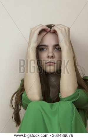 A Girl With Long Blonde Hair In A Green Dress Is Sad, She Is Depressed And Melancholy. A Girl With L