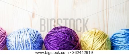 Multicolored Woolen Balls On Wooden Background. Banner With Botten Border. Knitting As Hobby. Purple
