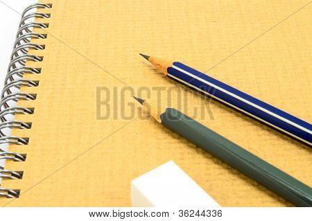 Two Wooden Pencil And Eraser On Recycle Notebook On White Background.