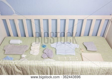 Set Of Clothing And Body Care Supplies For Newborns In Baby Crib. Collect The Bag In The Maternity H