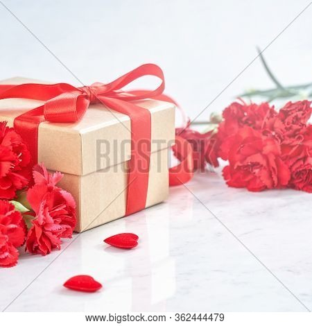 Mother's Day Gift Background, Red Carnation Flower Bouquet With Wrapped Kraft Gift Tied With Ribbon