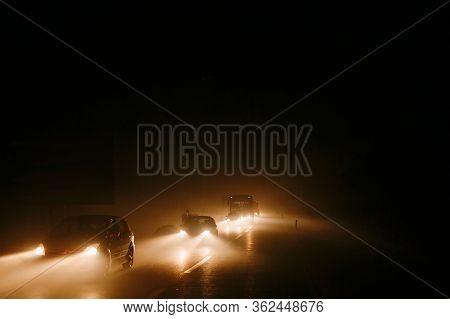 Traffic Jam In The Smoke. Light Of Car Headlights In Smoke From Fire