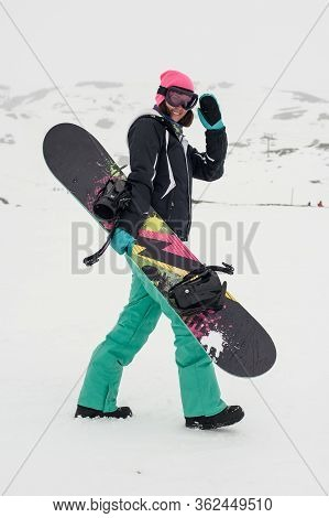 Snowboarder Girl Walk Through The Snow And Carries Her Snowboard