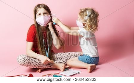 Personal Protective Equipment: Masked Sisters Play D Doctor, And The Younger Sister Treats The Older