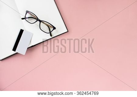 Notebook, Sketchbook, Eyeglasses, Credit Card Flat Lay In Minimal Style On Pink Background Top View