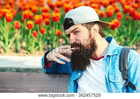 Bearded Hipster Smoking Cigarette Outdoors. Man Thinking About Something.
