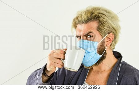 Wearing Mask Protect From Coronavirus. Guy In Mask Drink Tea Or Coffee At Home. Man Wear Face Mask.