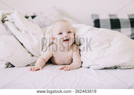 Little Baby Girl Lying On Soft White Blanket. Baby In White Sunny Bedroom. Newborn Child Relaxing In