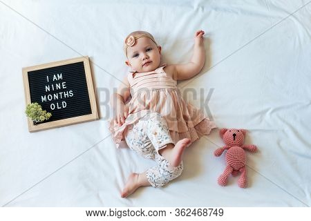 9 Nine Months Old Baby Girl Laying Down On White Background With Letter Board And Teddy Bear. Flat L