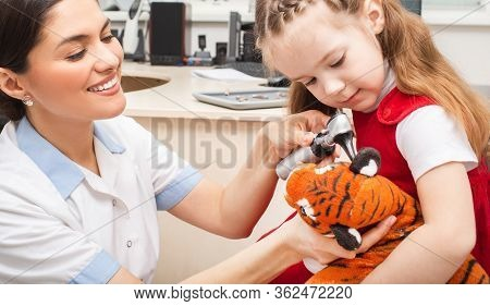 Otolaryngologist In A Playful From Doing A Hearing Exam To A Child Using Otoscope. Hearing Check -up