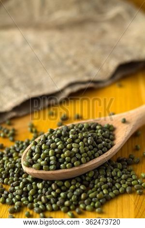 Green Mung Beans In Spoon With Sackcloth On A Yellow Background. Wooden Spoon With Dried Mung Bean A