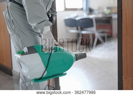 Disinfecting Of Office To Prevent Covid-19, Person In White Hazmat Suit With Disinfect In Office, Di