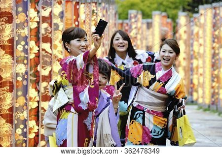 Kyoto,japan - November 5, 2014: Geisha Women In Traditional Dress Taking A Selfie With A Telephone.s