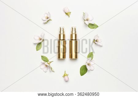Cosmetics Springtime Concept. Cosmetics, Spring White Flowers Green Leaves On Light Background. Cosm