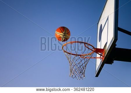 Street Basketball Ball Falling Into The Hoop. Close Up Of Orange Ball Above The Hoop Net With Blue S