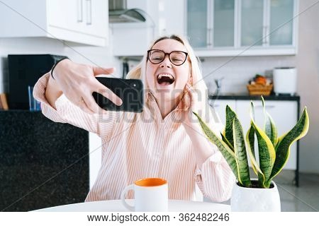 Happy Girl Sitting At Home Kitchen And Holding Videocall. Young Woman Using Smartphone For Video Cal