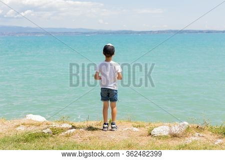 Boy Stands On Coast Of Lake, Sunny Daytime. Healthy Leisure. Summer. Calmness. Nature. Panoramic Vie