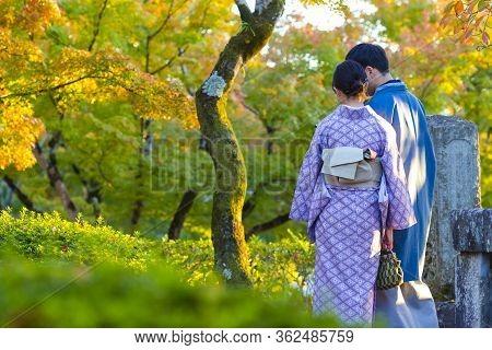 Japanese Destinations. Couple Of Japanese Geishas In Traditional Silk Kimonos Posing In Garden Of Ky