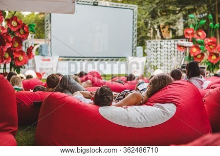 People At City Public Park Watching Movie At Open Air Cinema