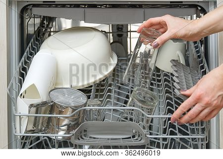 Woman Take Clean Drinking Glass From Dishwasher Machine. Woman Putts Drinking Glass To Dishwasher Ma