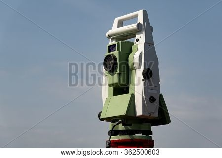 Geodetic Device. Electronic Total Station On A Tripod Against A Blue Sky.