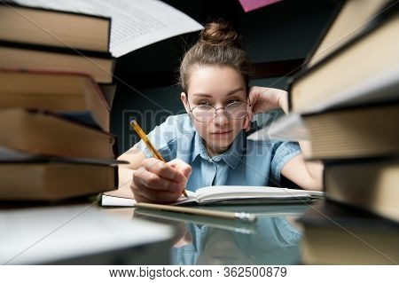 The Girl Is Studying Late At Home At Home At The Table On Which Lies A Large Number Of Books.