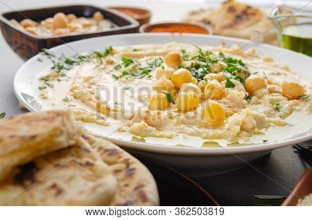 Closeup View At Hummus Topped With Beans Olive Oil And Green Coriander Leaves On Kitchen Table With