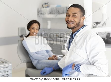 Visiting Dentist. Black Dentist Doctor And Female Patient In Chair Smiling At Camera, Clinic Interio