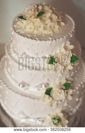 Three-tier Wedding Cake With Cream Roses And Green Foxes