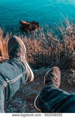 Legs Of Man In Jeans And Shoes Are Hanging From Edge Of Cliff Over The Sea And Trees
