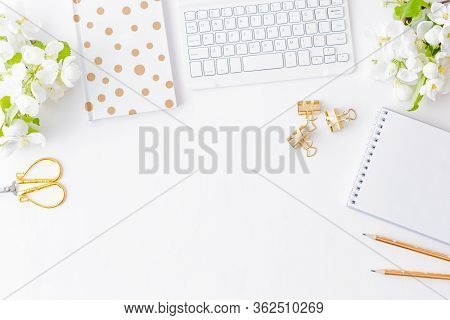 Flat Lay Blogger Or Freelancer Workspace With A Notebook, Keyboard And White Spring Flowers On A Whi