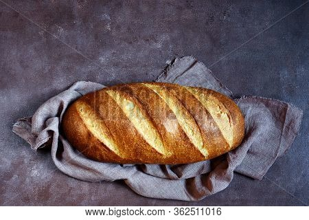 Fresh Loaf On A Brown Background.  Traditional Wheat Freshly Rustic Baked Bread, Loaf Of Bread.