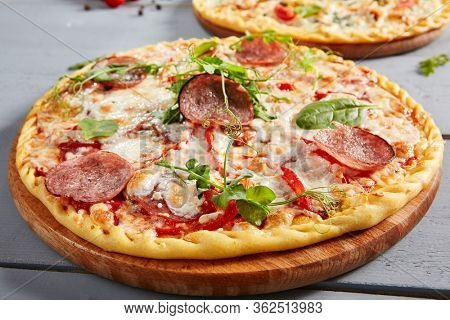 Prosciutto Funghi pizza on wooden board. Traditional italian cuisine bakery with salami, champignons, bell pepper, tomatoes, mozzarella and red tomato sauce close up. Hot snack, pizzeria meal