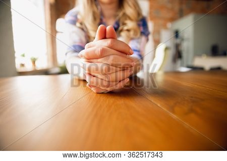 Woman Sitting At The Table With Her Hands Folded, Close Up. Businesswoman Or Housewife, Worker Durin