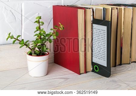 E-reader On A Shelf With Paper Books And Small Potted Plant. Copy Space On E-book Display. E-reading