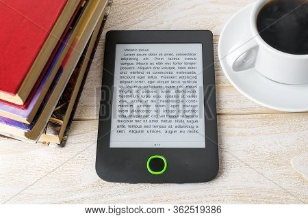 E-reader, Stack Of Ordinary Paper Books And Cup Of Hot Coffee On A White Wooden Table. Copy Space On