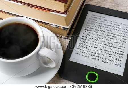 Close-up Of E-book Reader Near Cup Of Hot Coffee And Stack Of Ordinary Paper Books. Copy Space On E-