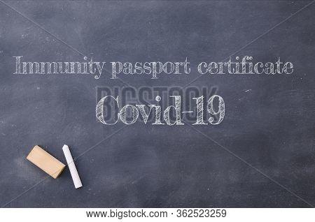 Immunity Passport Certificate Covid-19 Written On A Blackboard.