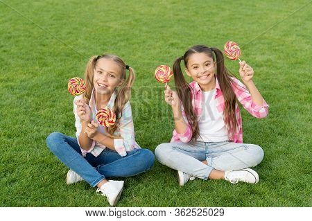 Candy Girls. Happy Children Hold Candy Green Grass. Candy Shop. Lollipop Or Sucker On Sticks. Sugary