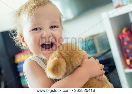 Cute Adorable Caucasian Blond Toddler Boy Having Fun, Laughing And Hugging Soft Puppy Toy Indoors. C
