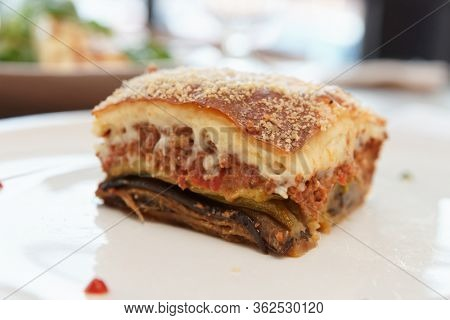 Slice of moussaka, traditional Greek dish, on white plate